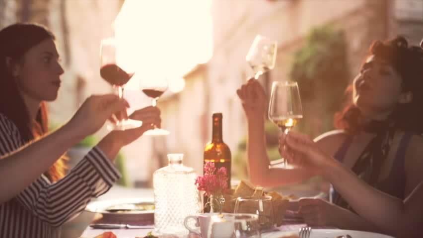 partia ľudí si prijíja vínom